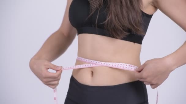 Young multi-ethnic woman measuring waist ready for gym
