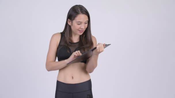 Young happy woman showing clipboard and giving thumbs up ready for gym