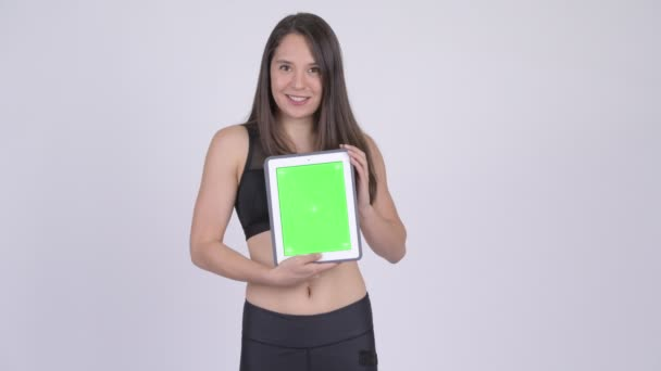Young happy multi-ethnic woman showing digital tablet ready for gym