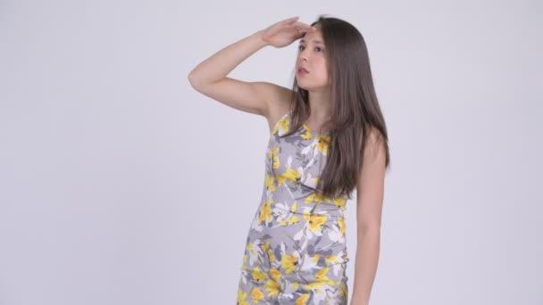 Young beautiful multi-ethnic tourist woman searching something
