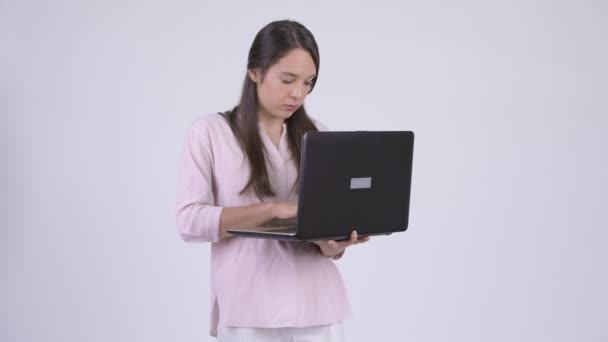 Young happy multi-ethnic businesswoman thinking while using laptop