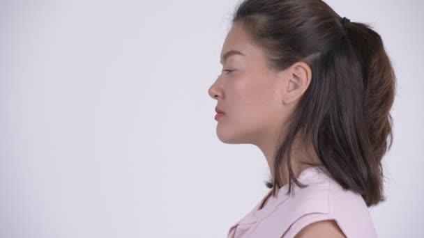 Closeup profile view of young beautiful Asian businesswoman thinking