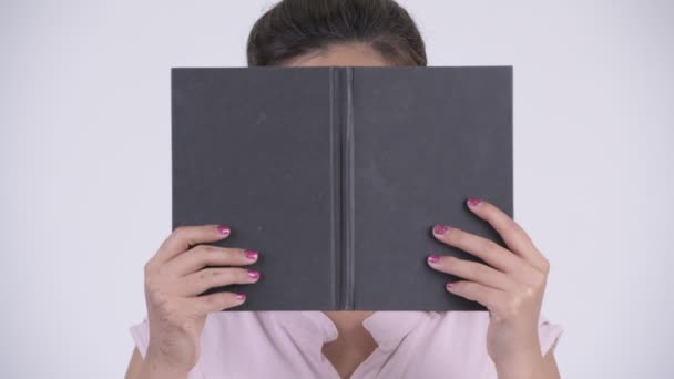 Face of young beautiful Asian businesswoman covering face with book