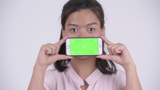 Face of young happy Asian businesswoman showing phone