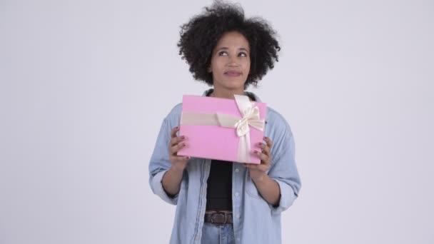 Mladá šťastná Afričanka myšlení podržíte-dárková krabička