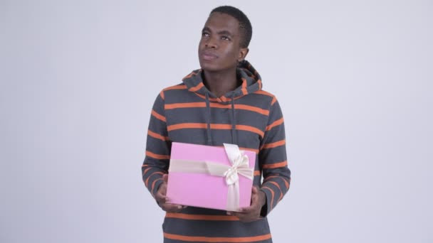 Young happy African man thinking while holding gift box
