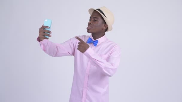 Young happy African tourist man video calling with phone