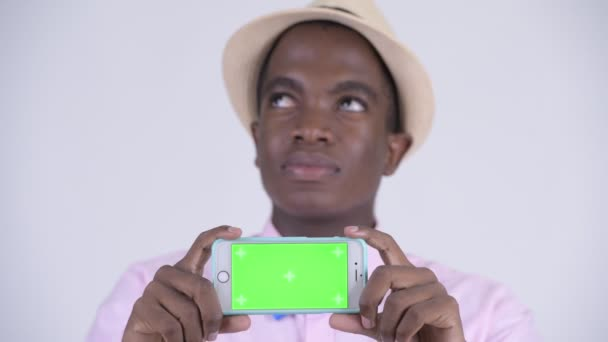 Face of young happy African tourist man thinking while showing phone