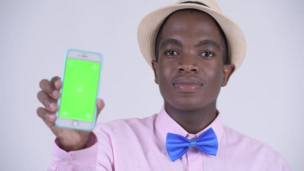 Studio shot of young handsome African tourist man against white background