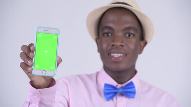 Face of young happy African tourist man showing phone