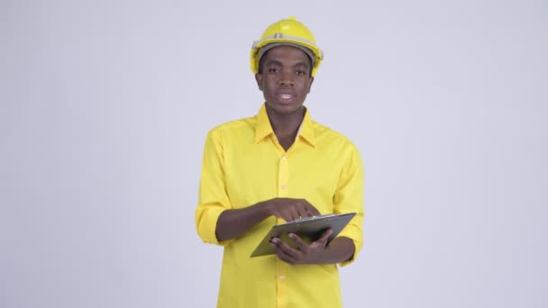 Young African businessman as engineer talking while reading on clipboard