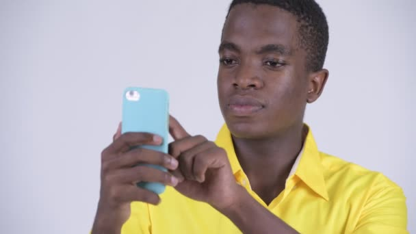 Face of young happy African businessman using phone