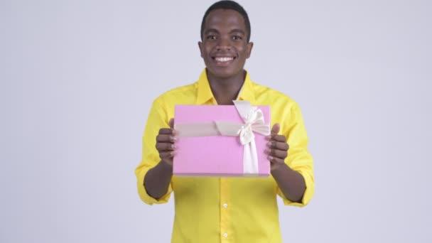 Studio záběr mladý hezký africké podnikatele na sobě žluté tričko proti Bílému pozadí