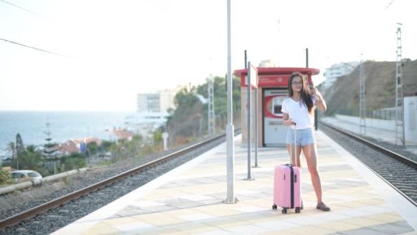 glücklich schöne asiatische Touristin macht Selfie, während sie am Bahnhof steht