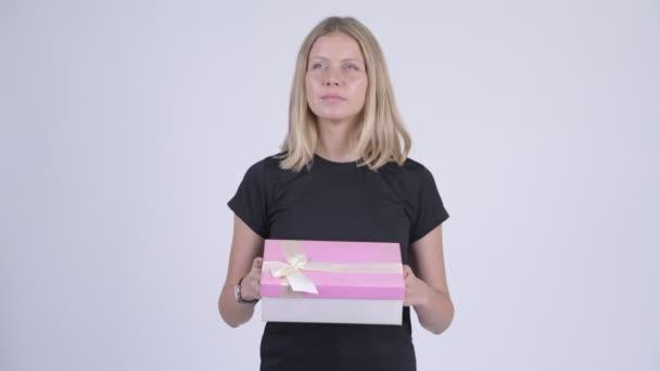 Mladá šťastné blond žena myšlení podržíte-dárková krabička