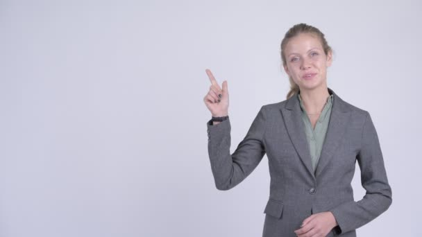 Young happy blonde businesswoman thinking and pointing up