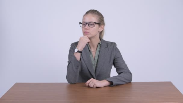 Young beautiful blonde businesswoman thinking while sitting behind desk