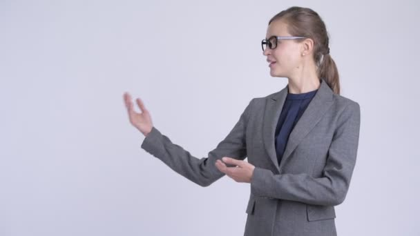 Young happy businesswoman with eyeglasses showing something