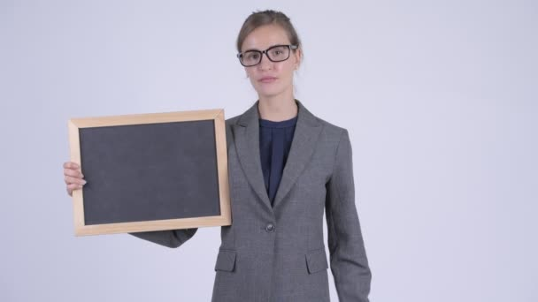 Young stressed businesswoman giving thumbs down while holding blackboard