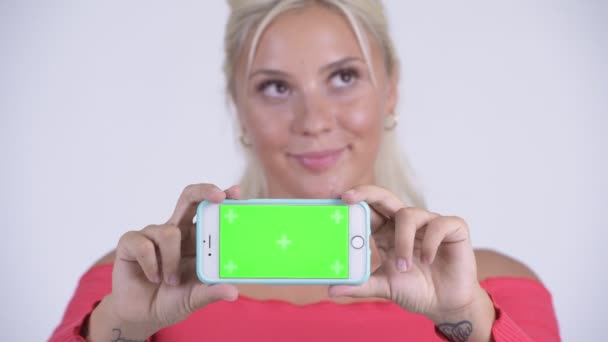 Face of happy young beautiful blonde woman thinking while showing phone