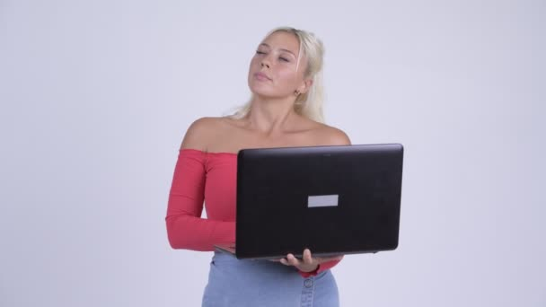 Happy young beautiful blonde woman thinking while using laptop