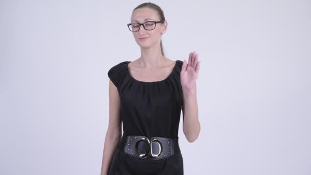 Happy blonde businesswoman with eyeglasses waving hand