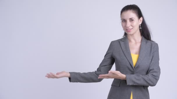 Happy young beautiful businesswoman showing something