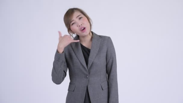 Young happy Asian businesswoman with call me gesture