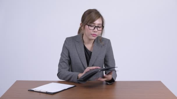 Young beautiful Asian businesswoman reading on clipboard and book at desk
