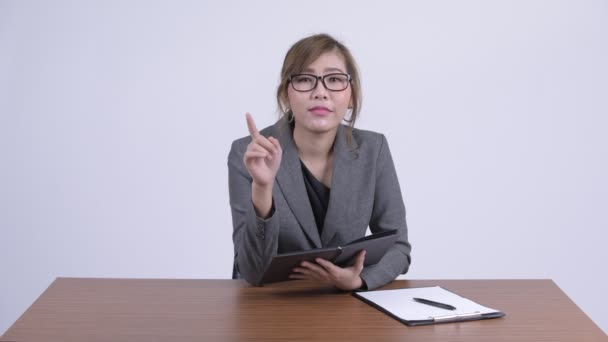 Young happy Asian businesswoman talking while writing on book at desk