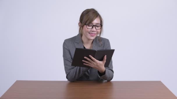 Young happy Asian businesswoman reading book at desk