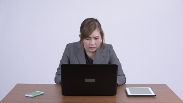 Young beautiful Asian businesswoman video calling at work