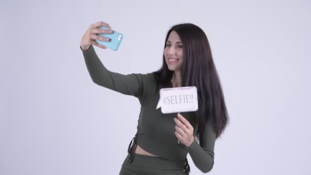 Happy young beautiful woman taking selfie with paper sign