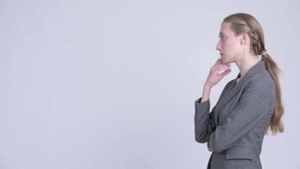 Profile view of happy young blonde businesswoman thinking