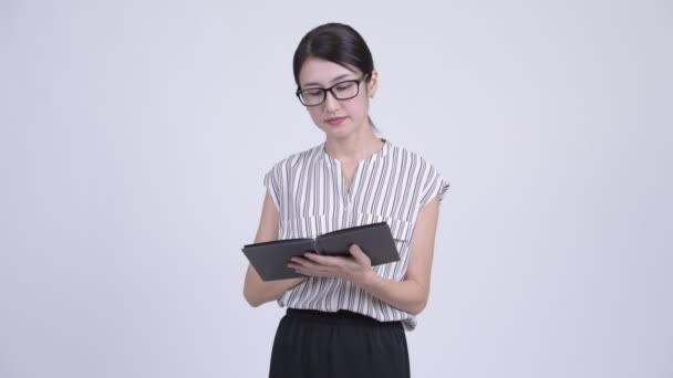 Shy Asian businesswoman covering face with book