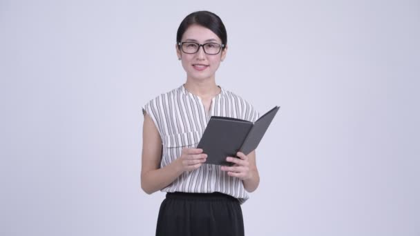 Happy beautiful Asian businesswoman as teacher reading book