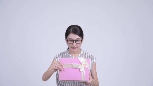 Happy beautiful Asian businesswoman opening gift box and looking surprised