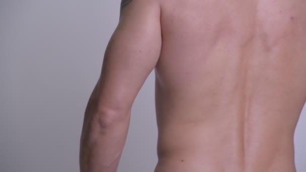 Svalová hezký vousatý muž protahuje svaly košili