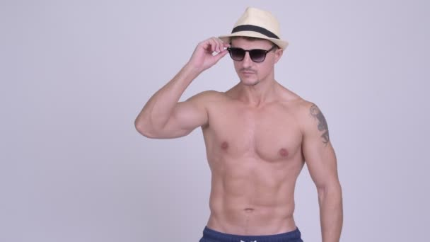 Happy muscular tourist man looking surprised and waving hand shirtless