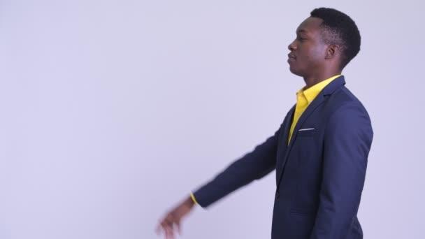 Profilové zobrazení mladého šťastného afrického obchodníka ukazovacího prstem