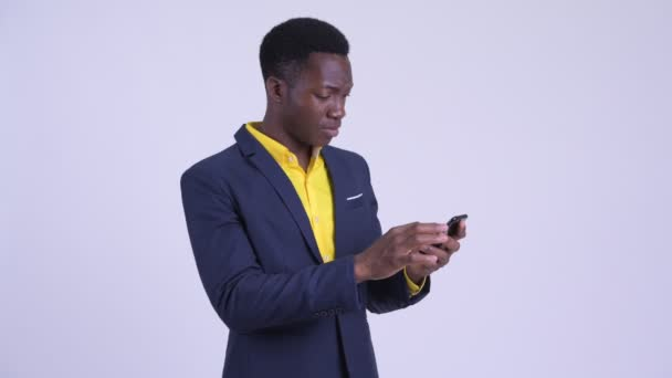 Young happy African businessman using phone and getting good news