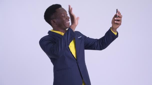 Mladý šťastný africký podnikatel video volá s telefonem