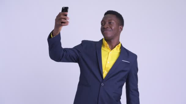 Young happy African businessman taking selfie