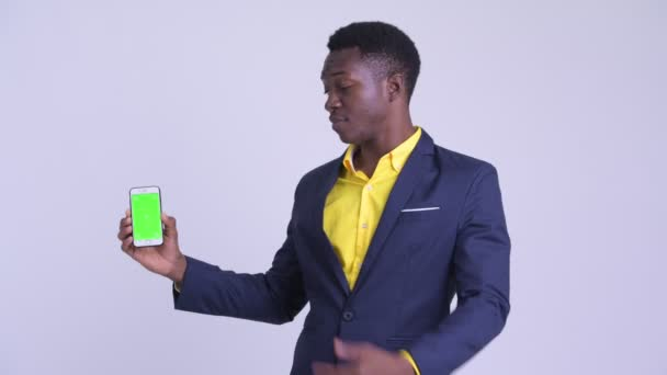 Young happy African businessman showing phone and giving thumbs up