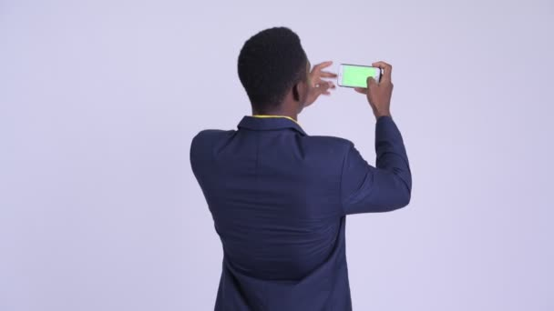 Rear view of young happy African businessman taking picture with phone