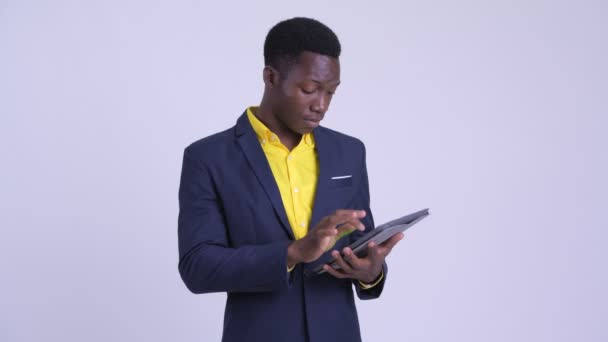Young happy African businessman using digital tablet and getting good news