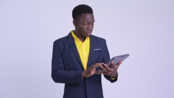 Young stressed African businessman using digital tablet and getting bad news