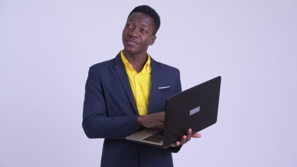 Mladý šťastný africký podnikatel myšlení při používání notebooku