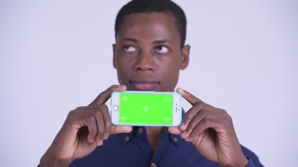Face of young happy African businessman thinking while showing phone
