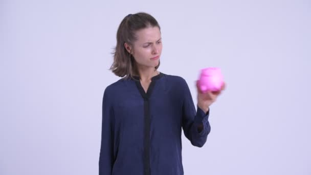 Sad young businesswoman shaking piggy bank and looking upset